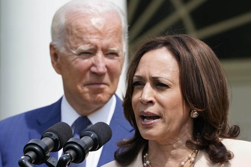 President Joe Biden, left, listens to Vice President Kamala Harris, right, speak at an event in the White House Rose Garden.