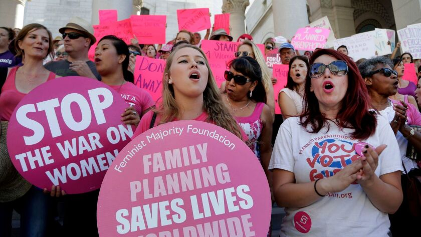 """Planned Parenthood supporters rally for women's access to reproductive health care on """"National Pink Out Day'' at Los Angeles City Hall in 2015."""
