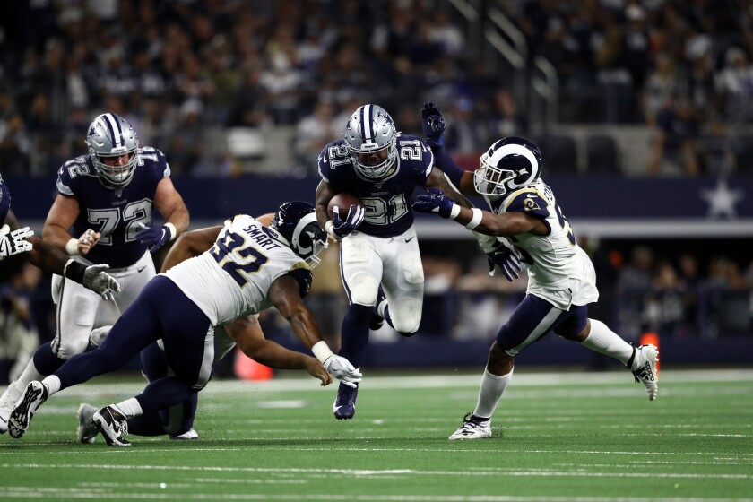 The Cowboys' Ezekiel Elliott runs through the Rams defense, as the running back did for most of the afternoon.