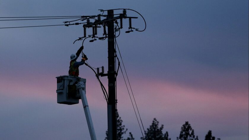 FILE - In this Nov. 26, 2018, file photo, a Pacific Gas & Electric lineman works to repair a power l