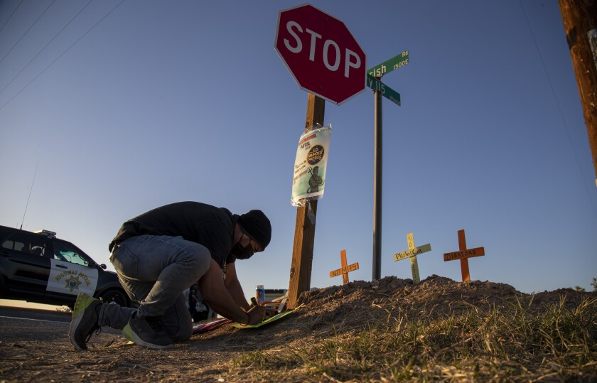 A man kneels to place wooden crosses in the dirt
