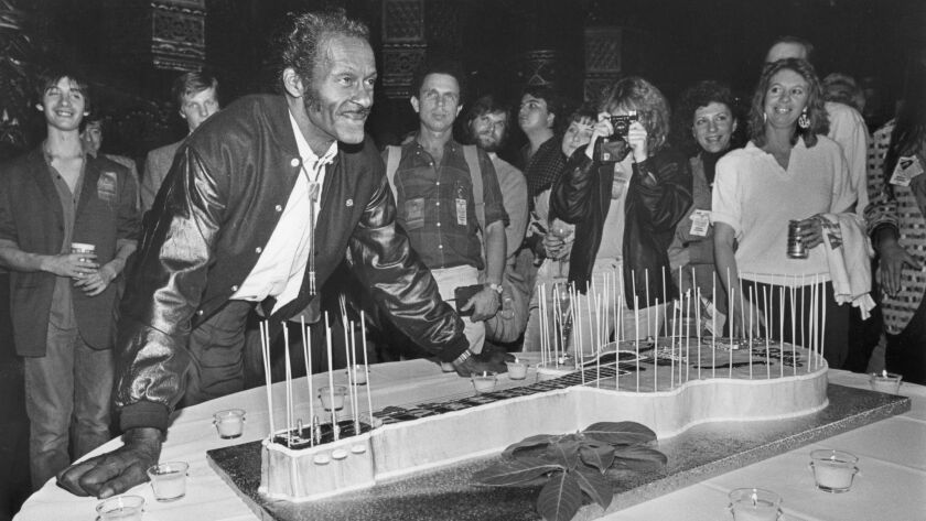Chuck Berry, shown in St. Louis with a guitar-shaped cake for his 60th birthday in 1986, elevated the vocabulary of rock music from the outset in the 1950s.