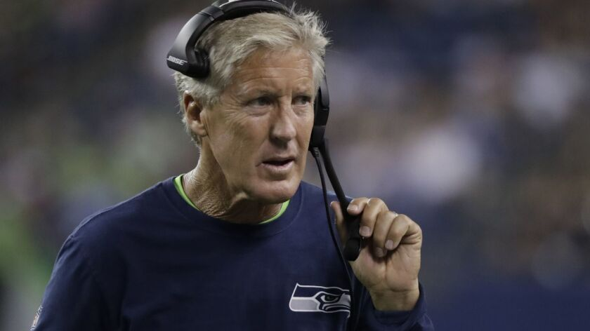 Seattle Seahawks head coach Pete Carroll holds his headset during the second half of an NFL football