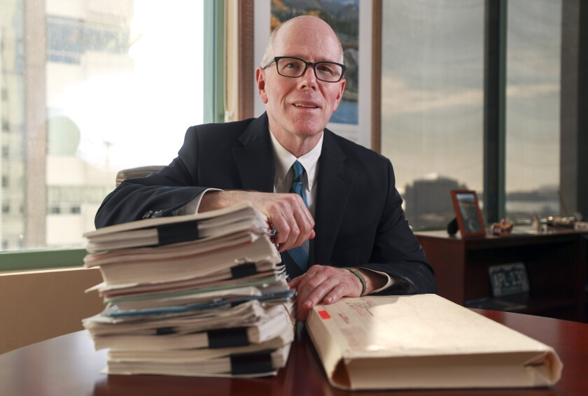 Deputy District Attorney Brent Neck with a stack of files from his 1996 prosecution of Jonathan Simmons, at his office at the Hall of Justice.