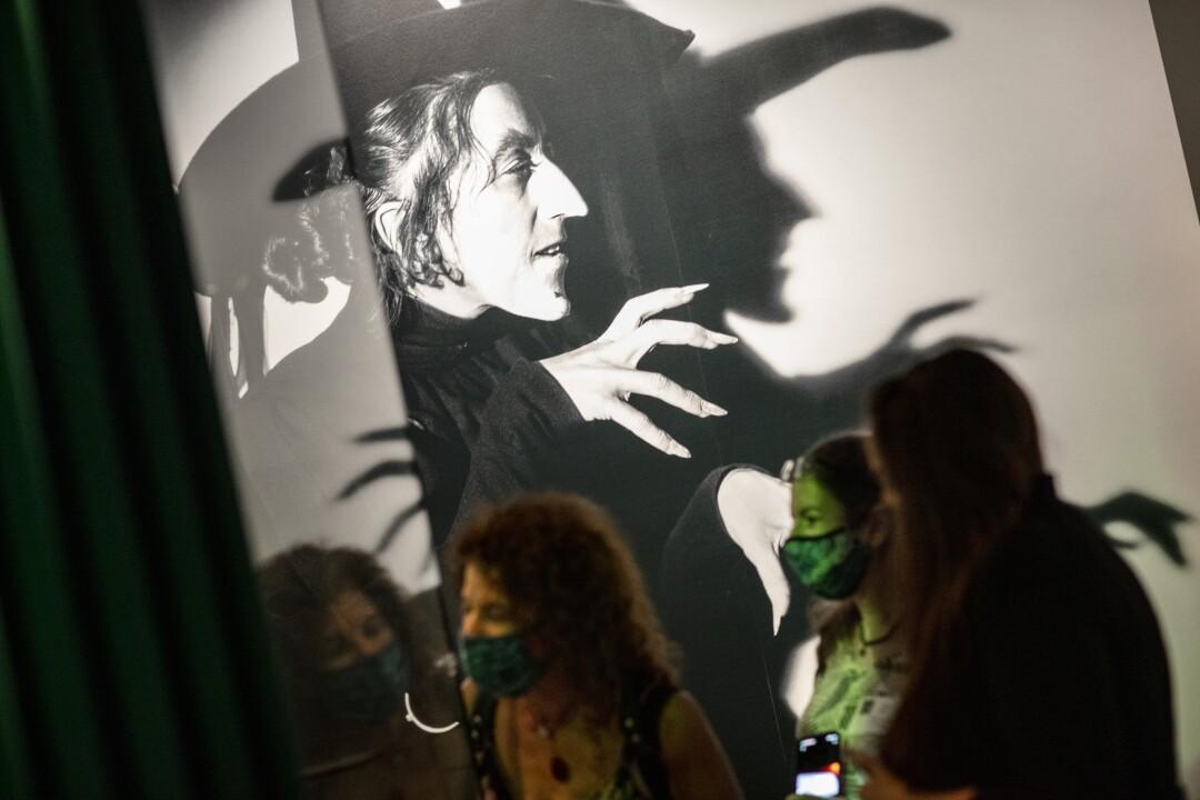 Los visitantes se paran frente a una gran imagen de una bruja.