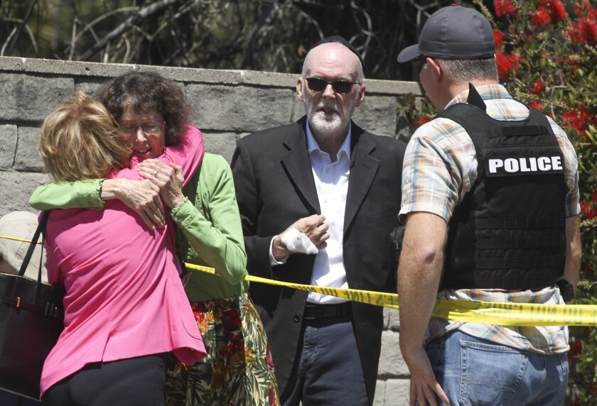 Chabad of Poway members hug after a 19-year-old gunman shot multiple people inside the synagogue.