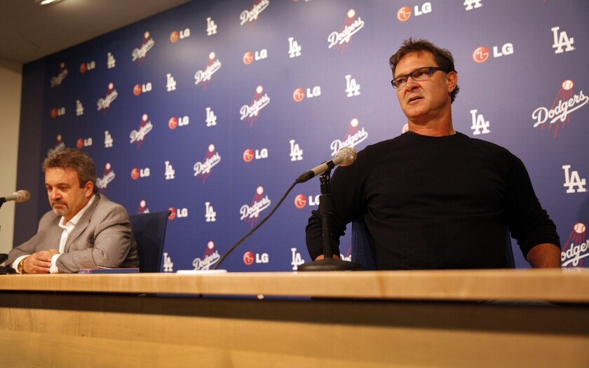 Dodgers Manager Don Mattingly, right, speaks at a news conference while sitting near Dodgers General Manager Ned Colletti on Monday. Mattingly is not happy with his current contract situation with the team.