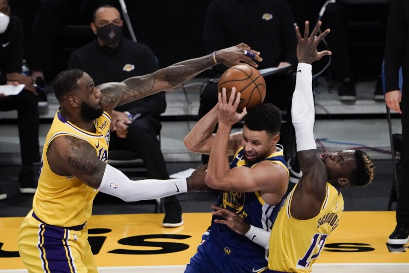 Lakers forward LeBron James and guard Dennis Schroder defend against Golden State Warriors guard Stephen Curry.