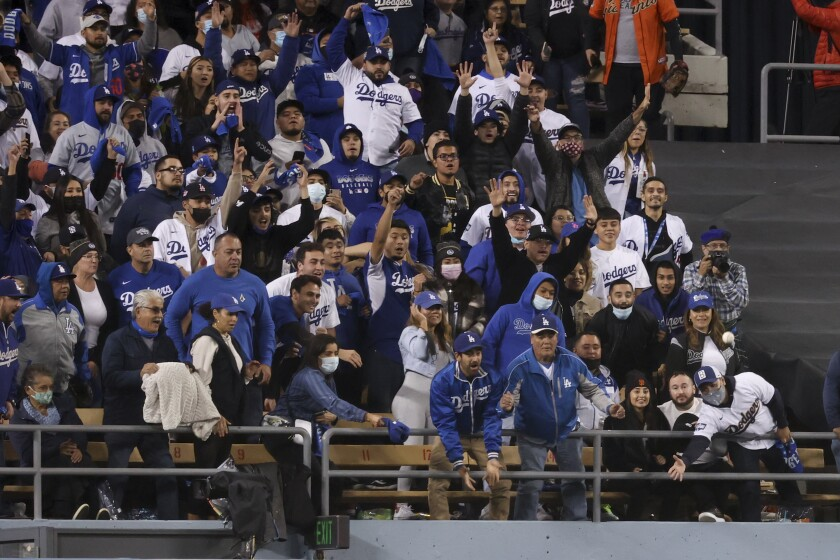 Fans in the pavilion reach for a two-run home run ball hit by Will Smith in the eighth inning of the Dodgers' 7-2 win.
