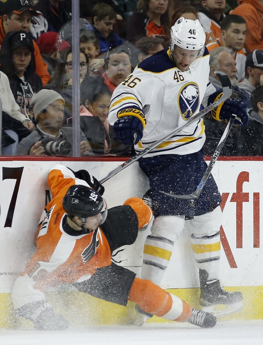 Buffalo Sabres' Cody Franson, right, knocks down Philadelphia Flyers' Jordan Weal during the first period of an NHL hockey game, Thursday, Feb. 11, 2016, in Philadelphia. (AP Photo/Matt Slocum)