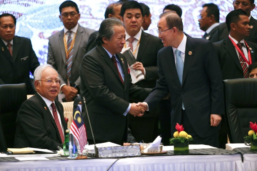 Malaysian Foreign Minister Anifah Aman, second from left, shake hands with U.N. Secretary General Ban Ki-moon while Malaysian Prime Minister Najib Razak, seated, looks on during the 10th East Asia Summit at the 27th ASEAN Summit in Kuala Lumpur, Malaysia, Sunday, Nov. 22, 2015. (AP Photo/Vincent Thian)