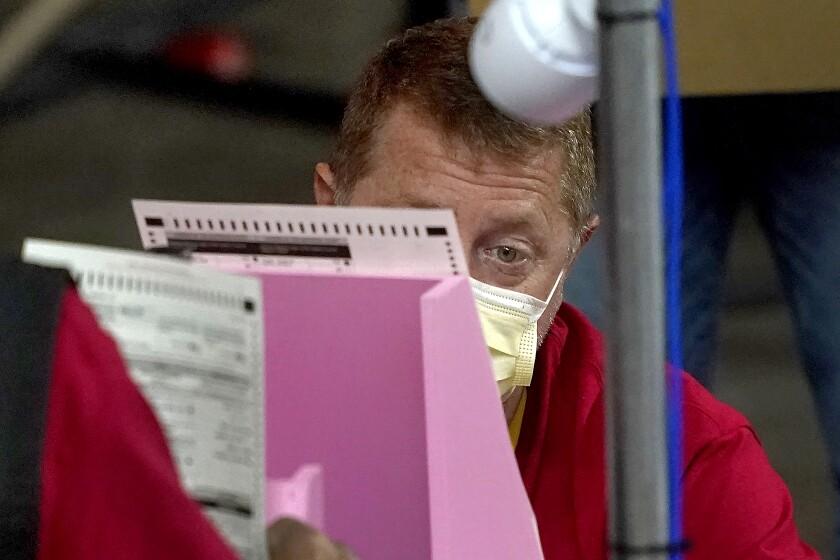 Contractors for Cyber Ninjas look at ballots at Veterans Memorial Coliseum in Phoenix.
