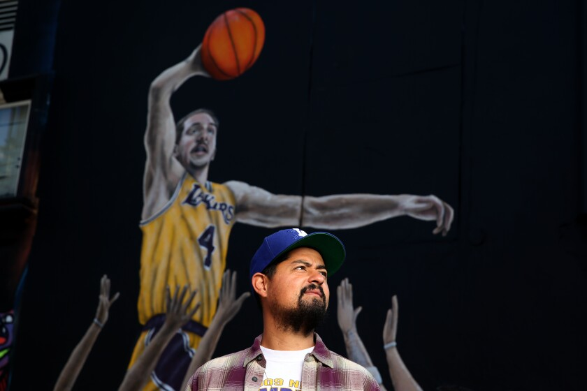 Artist Gustavo Zermeño Jr. in front of a mural he painted of Lakers guard Alex Caruso and other basketball players of the West Coast in the parking lot of Sportie LA.