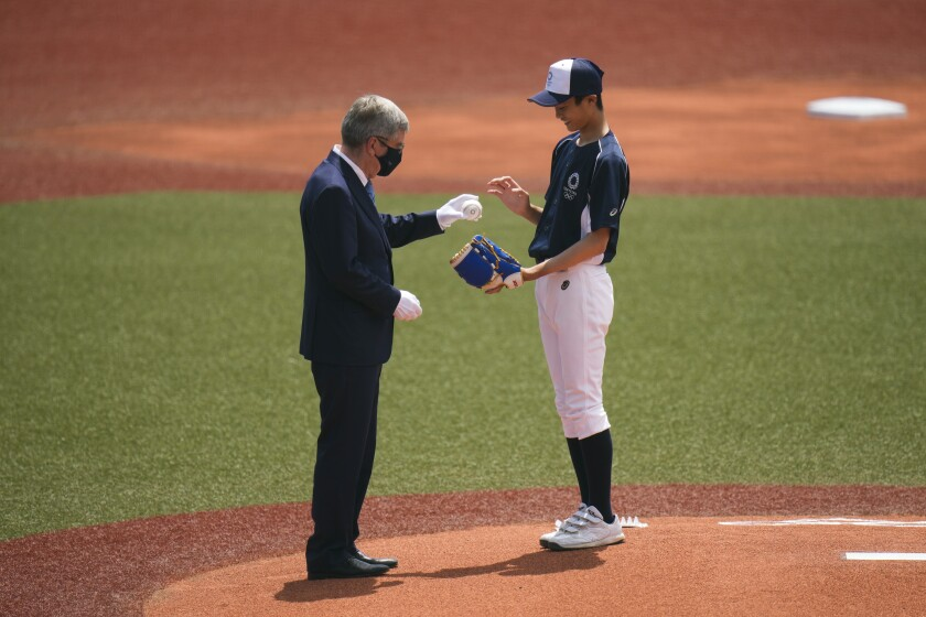 International Olympic Committee President Thomas Bach, left, hands the ball to Yuma Takara, 14, during a pre-game ceremony before a baseball game between Japan and the Dominican Republic at the 2020 Summer Olympics, Wednesday, July 28, 2021, in Fukushima, Japan. (AP Photo/Jae C. Hong)