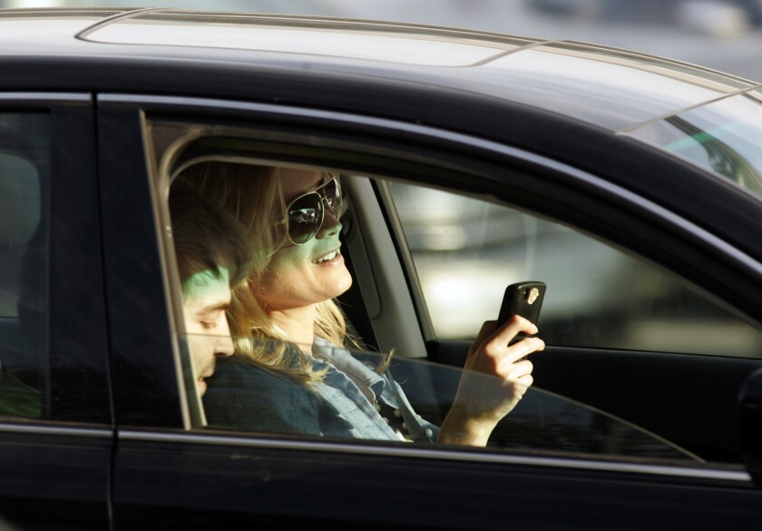 A motorist appears to be texting, while driving thru the intersection of Santa Monica and Wilshire Boulevards in Beverly Hills.