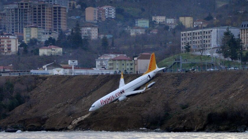 A Pegasus Airlines jet sits on a slope just above the sea after skidding off the runway in Trabzon.