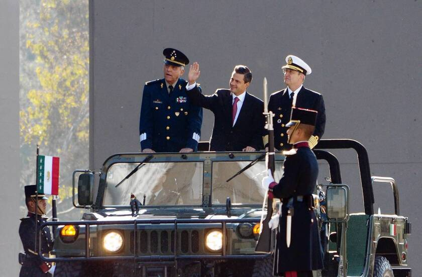 Mexican President Enrique Peña Nieto reviews military troops in Mexico City. With him is Defense Minister Gen. Salvador Cienfuegos, left, and secretary of the navy, Adm. Vidal Soberon.