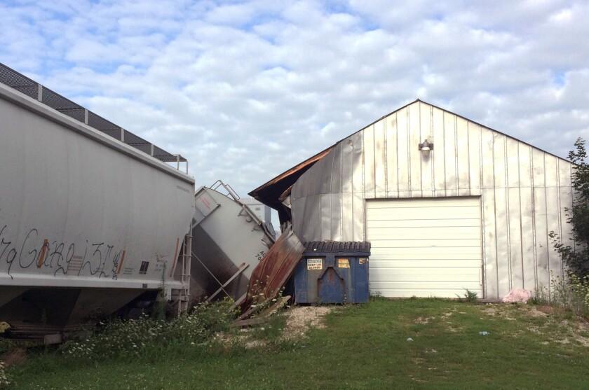 Un vagón de carga de un tren que descarriló en Charles City, en el norte de Iowa, y dañó una taberna llamada Descarrilado. Nadie resultó herido. (Kate Hayden/Charles City Press vía AP)
