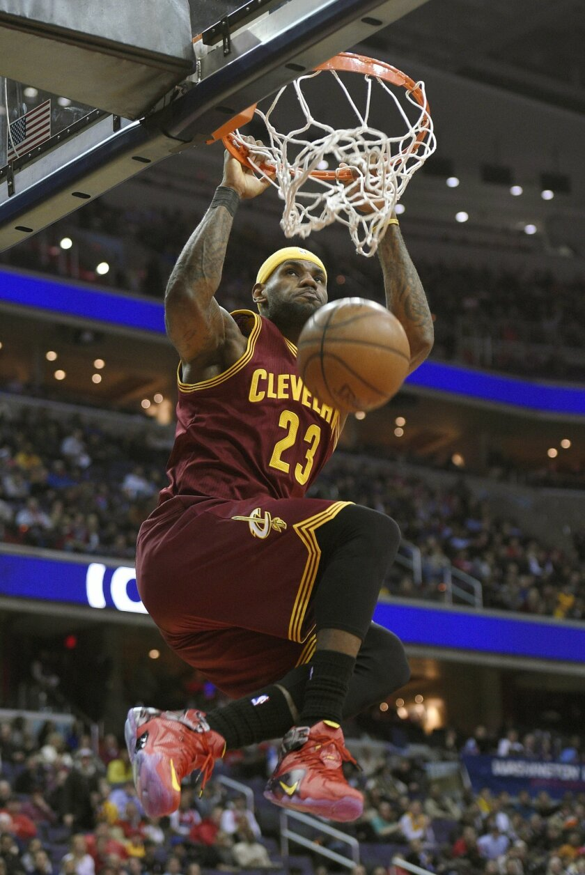 RETRANSMISSION TO CORRECT YEAR - Cleveland Cavaliers forward LeBron James (23) dunks during the first half of an NBA basketball game against the Washington Wizards, Friday, Feb. 20, 2015, in Washington. (AP Photo/Nick Wass)