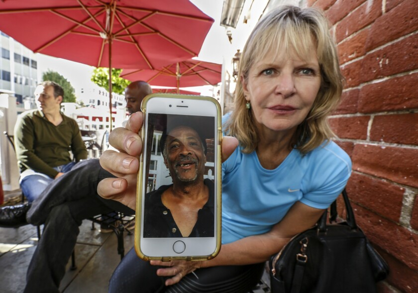 Maria Belknap shows a photo of George Saville on her phone. Belknap is part of a group of Beverly Hills cafe-goers who have embraced Saville, who is homeless and has run afoul of city officials.