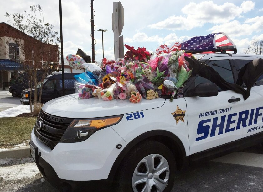 Tributes in memory of two slain deputies are stacked on a Harford County Sheriff's Office Department vehicle outside the department's southern precinct, Thursday morning, Feb. 11, 2016, in Edgewood, Md. David Evans, who had warrants for his arrest, fatally shot a deputy in a restaurant Wednesday, F