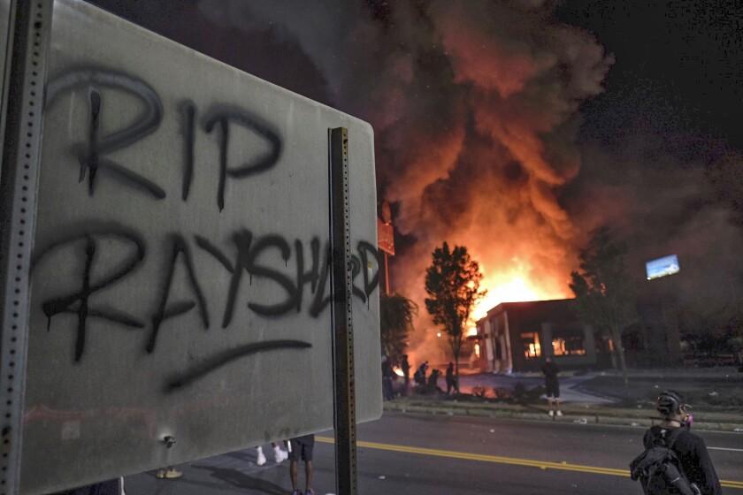 A Wendy's restaurant, background, burns Saturday, June 13, 2020, in Atlanta