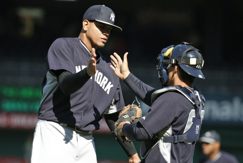 New York Yankees relief pitcher Dellin Betances, left, celebrates with catcher John Ryan Murphy (66) after an exhibition baseball game against the Washington Nationals at Nationals Park, Saturday, April 4, 2015, in Washington. The Yankees won 4-3. (AP Photo/Alex Brandon)