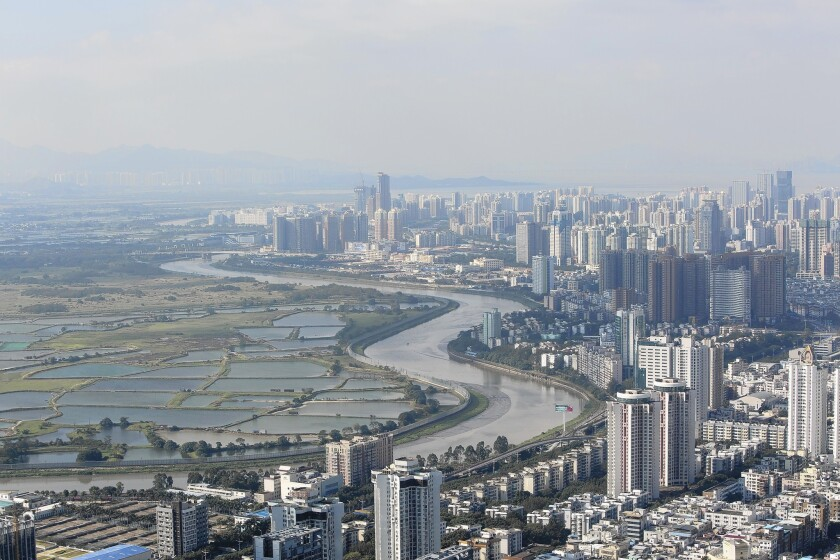 The Shenzhen River separates the high-rises of Shenzhen, China, from farmland in Hong Kong. China has come under criticism for the amount of agricultural land it has paved over in its push for economic development.