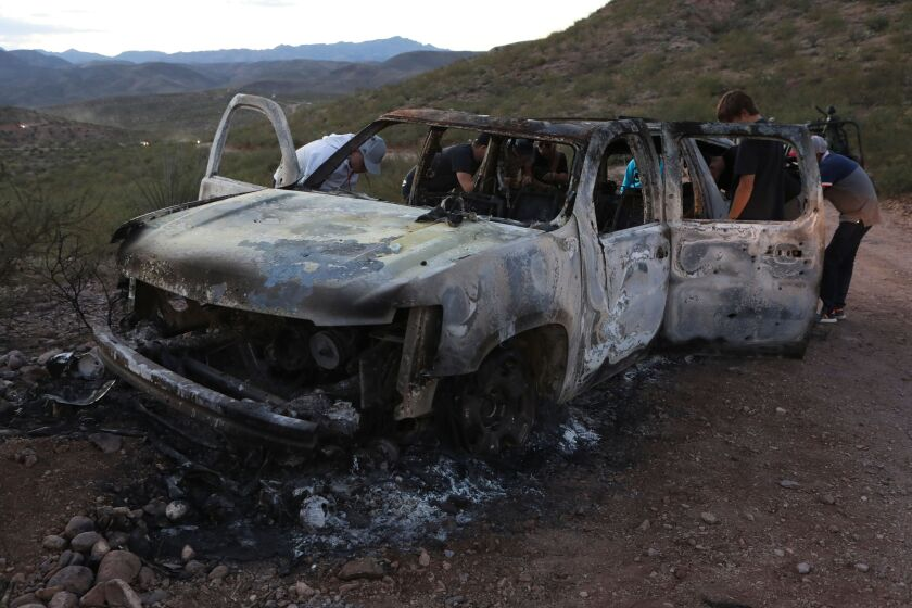 Relatives of three women and six children killed in an attack in Sonora on Nov. 4 inspect a vehicle that was charred during the ambush.