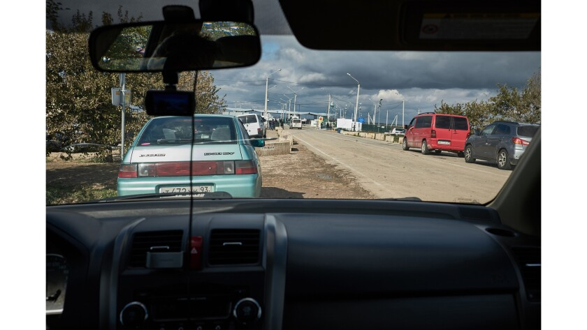 ONE TIME USE - Cars wait across the border in Russian-occupied Crimea for passengers to clear passpo