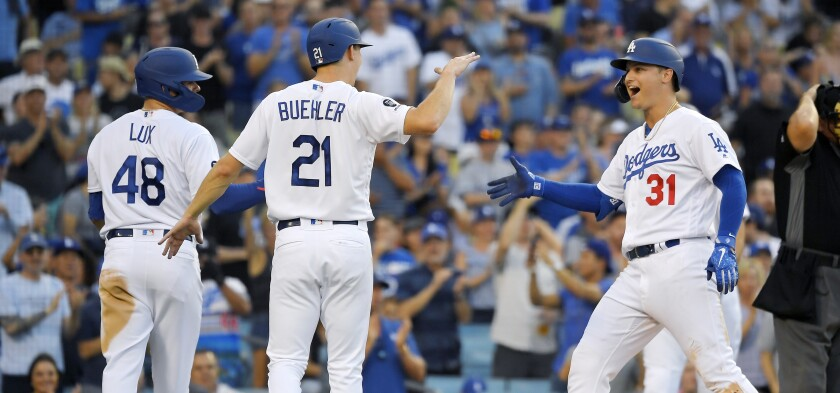 Dodgers right fielder Joc Pederson, right, is congratulated by teammates Gavin Lux, left, and Walker Buehler.