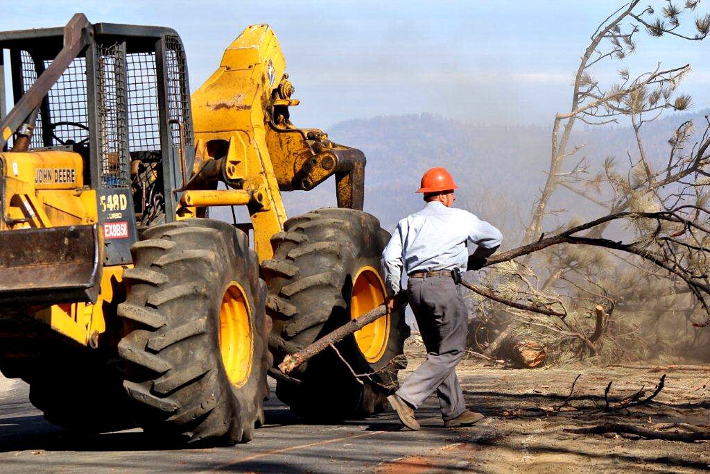 Sam Cover, 40, removes a snag from Cherry Oil Road near the community of Groveland, about 120 miles west of Yosemite National Park. Cover was a member of a crew doing emergency contract work for San Francisco Water and Power in a portion of the Stanislaus National Forest damaged by the Rim fire.