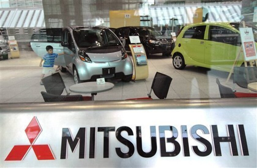 In this Aug. 2, 2006 file photo, a boy touches a vehicle displayed at Mitsubishi Motors Corp. headquarters in Tokyo. Mitsubishi Motors will slash more than 2,000 temporary jobs in Japan by the end of March as the country's fourth largest automaker struggles in the face of a severe slump in sales w