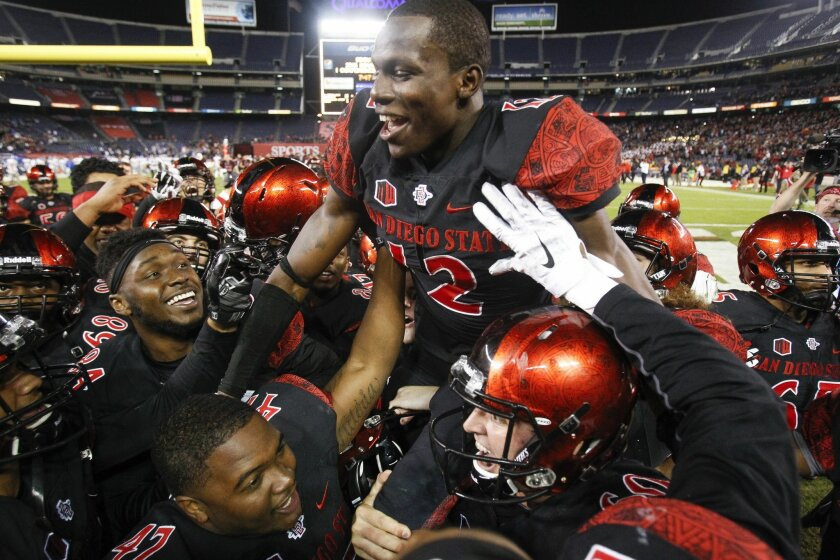 The Aztecs' Malik Smith is raised up by teammates as the Aztecs celebrate their 27-24 win over Air Force to win the Mountain West conference championship at Qualcomm Stadium.