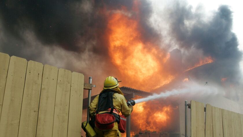 A firefighter tries to knock down flames on a home completely engulfed in hopes of saving neighboring homes in Rancho Bernardo during the 2007 wildfires.