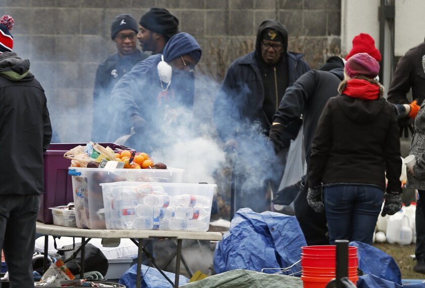 Protesters hang around the warming fire, Thursday, Nov. 19, 2015, at the Black Lives Matter encampment outside the Minneapolis Police Department's Fourth Precinct in Minneapolis. The fatal shooting of Jamar Clark, an unarmed black man by a Minneapolis police officer, has pushed racial tensions in the city's small but concentrated minority community to the fore, with the police precinct besieged by the makeshift encampment and many protesters.(AP Photo/Jim Mone)