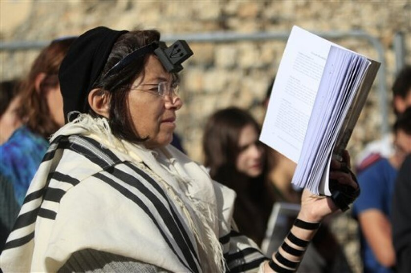 Israeli women of the Women of the Wall organization pray just outside the Western Wall, the holiest site where Jews can pray in Jerusalem's old city, Friday, Dec. 14, 2012. Security guards at the Western Wall, the holiest place where Jews can pray, usually search worshippers for weapons upon enteri