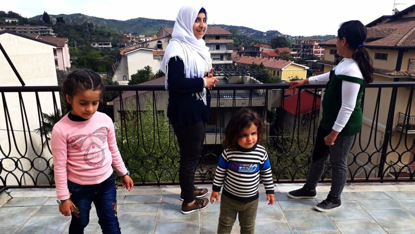 From left, Ghima, 7; Mais, 15; Bader, 2; and Ghazal, 11, stand on the rooftop terrace in their family's new home in the southern Italian town of Gioiosa Ionica.