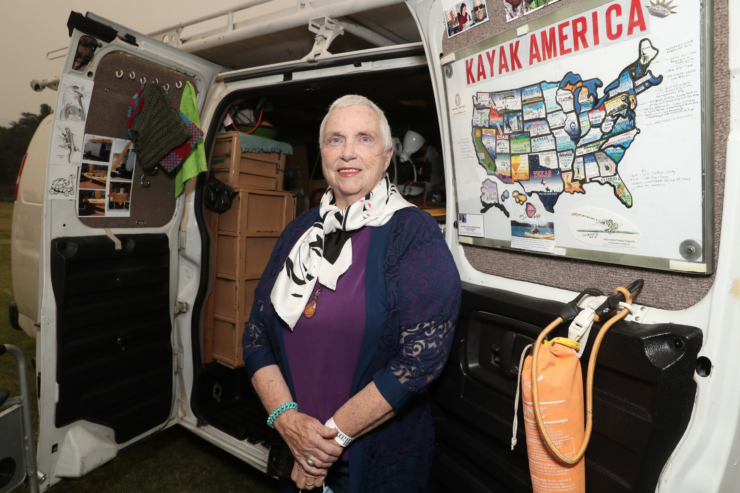 """Charlene Swankie stands at the back of her van at the """"Nomadland"""" drive-in premiere at Pasadena's Rose Bowl."""