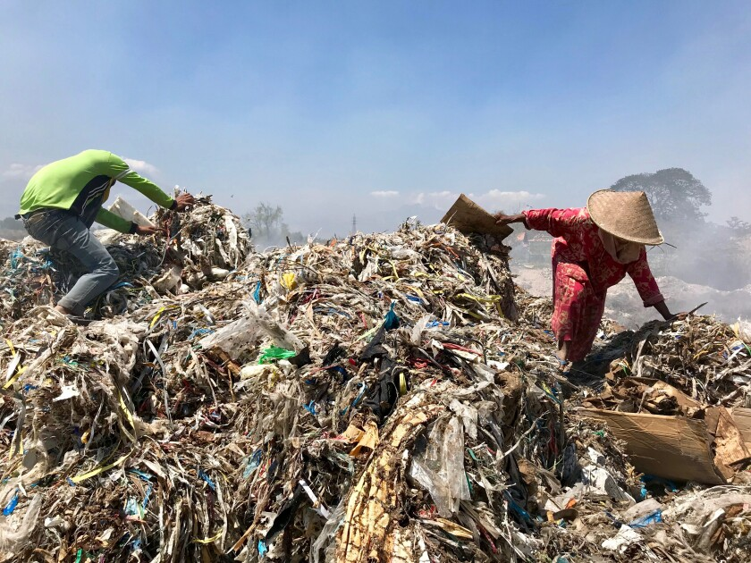 Scavengers pick through a mound of rubbish in Bangun.