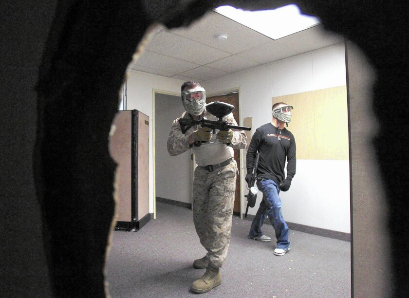 Warfighter Academy student Jason Perry (left) and instructor Joe Smith drill on close-quarters combat inside the new training center, which is the former Escondido Police Department headquarters on Grand Avenue.