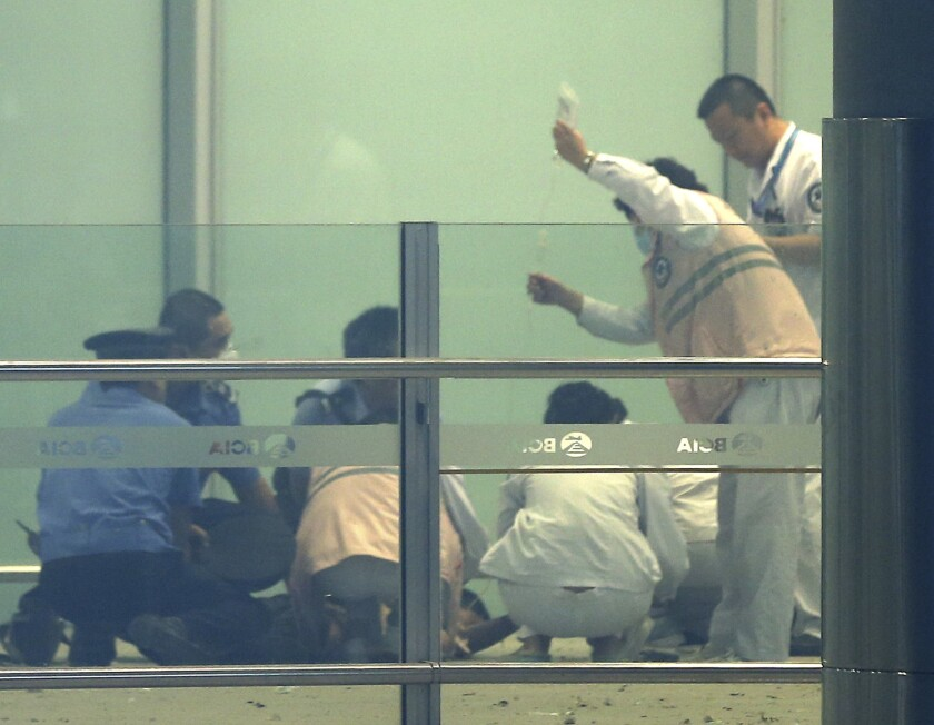 Medical workers and policemen work at terminal 3 of Beijing International Airport on Saturday after a man allegedly set off a homemade bomb, injuring himself but no one else.