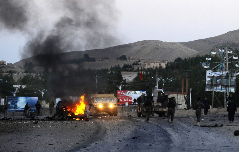 Smoke rises from a burning vehicle near the U.S. Consulate after an attack by a car bomb followed by a gunfight in Herat, Afghanistan. Seven heavily armed Taliban suicide attackers struck the consulate before dawn, setting off two car bombs and sparking a shootout with U.S. forces.