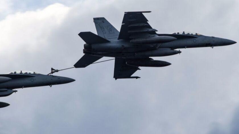 An F/A-18F Super Hornet refuels an EA-18G Growler
