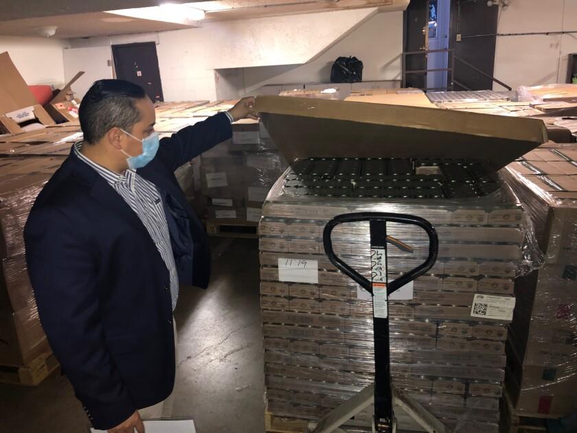 Tekandi Paniagua, cónsul general de Guatemala en L.A., muestra los donativos.