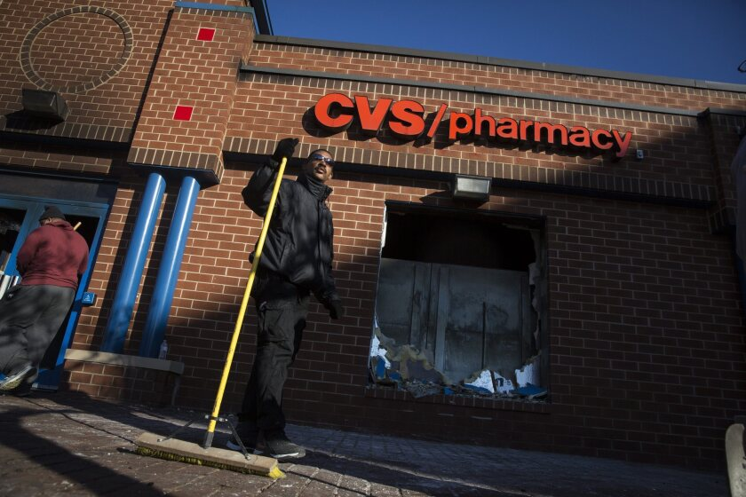 People clean up outside a CVS pharmacy in Baltimore after the pharmacy was set on fire in the wake of protests for the death of Freddie Gray.