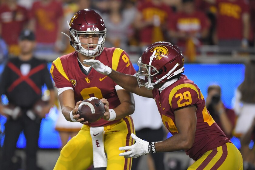 USC quarterback Kedon Slovis, left, hands off to running back Vavae Malepeai during the Trojans' win over Fresno State on Saturday.