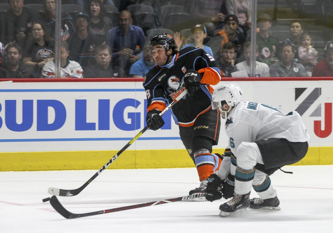 The Gulls' Kiefer Sherwood, left, shoots the puck to score a goal as San Jose's Ryan Merkley defends during the first period.