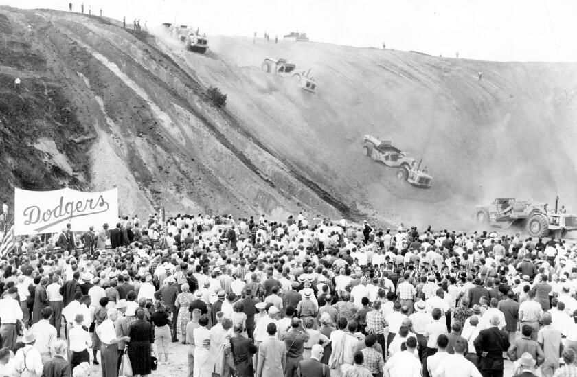 Une foule regarde en 1959 alors que des camions et des tracteurs roulent sur ce qui allait devenir le stade Dodger