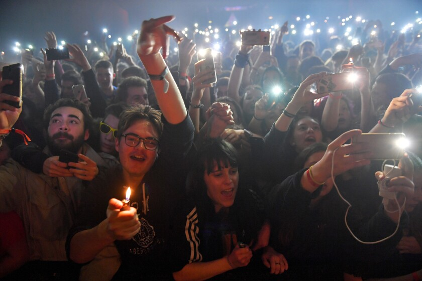 Concertgoers holding up lighters and phones